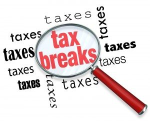 A magnifying glass hovering over the word tax breaks, symbolizin